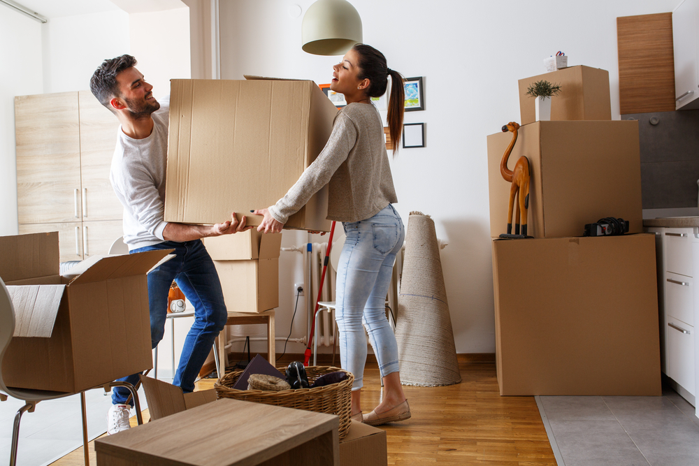 New homeowners carrying moving boxes into their new kitchen