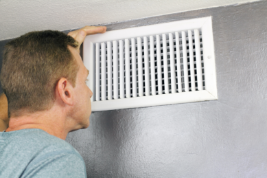 Man Looking At His Home Air Duct