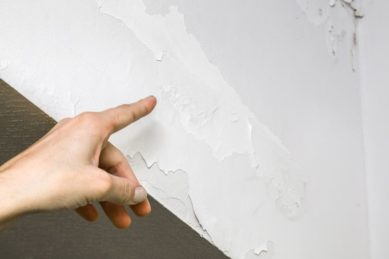 Woman's Hand Finger Pointing To Shabby Wall Defects Near The Roof Window Due To Humidity Problems